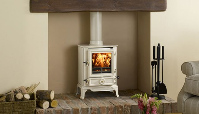 Creme woodburning stove in a living room, with logs next to it.